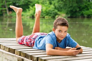 Freundlicher Jungendlicher mit Smartphone am idyllischen Teich