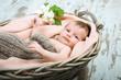 Baby mit Blüte im Korb