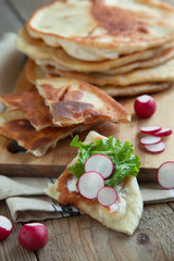 Homemade milk flatbread with cream cheese, lettuce and radish
