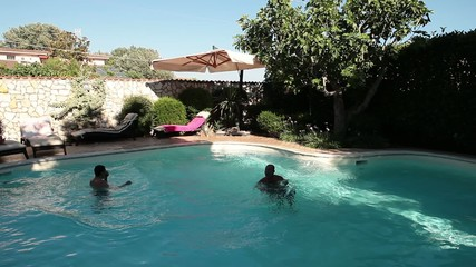 Two Men Side Jumping In The Pool