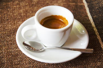 Cup of espresso over brown tablecloth