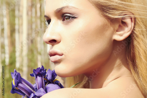 Beautiful blond woman with blue flowers in forest