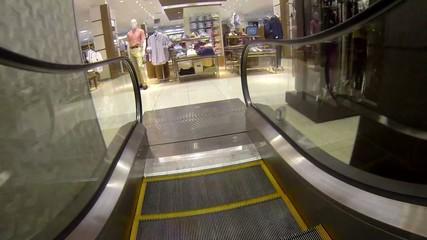 Shopping center area riding down escalator to the clothes area