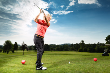 Young golf player on course doing golf swing