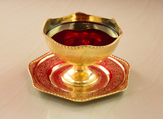 Golden bowl with red wine on a marble table