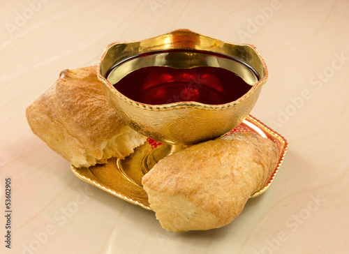 golden chalice with red wine and bread broken into on a marble t