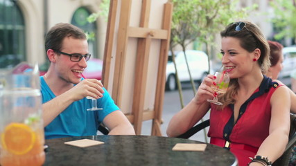 Happy young couple raising toast with drink in cafe