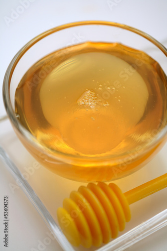 Honey jar and a honey dipper on white background