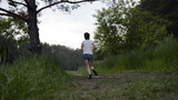 Young woman runs through forest and stops