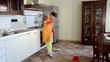 young woman cleaning the kitchen floor
