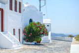 Fototapety Beautiful paved street with old traditional white house in Fira,