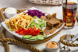 Closeup of vegetables, fries and meat kebab on a plate