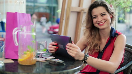 Cheerful woman with tablet computer in cafe