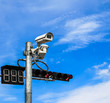 surveillance camera and traffic light against blue sky
