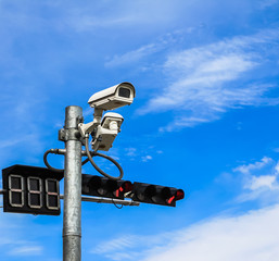 surveillance camera and traffic light against blue sky