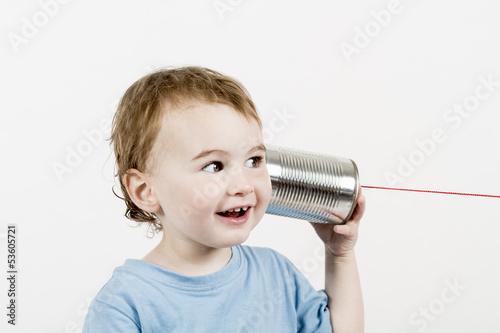 Leinwanddruck Bild friendly child listening to tin can phone