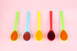 Baby puree in spoons on pink background