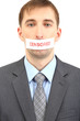 Young businessman with a band on his mouth isolated on white