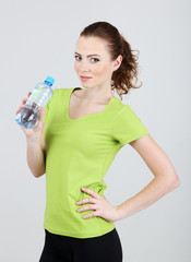 Beautiful young woman with bottle of water