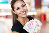young woman holding fan of cash in casino