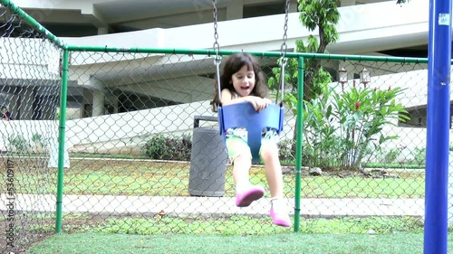 slow motion, a little girl swings on a swing set