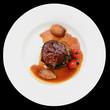 Tenderloin steak in plate, isolated on black