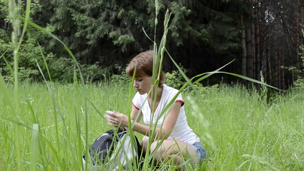 Young hiker girl searching phone in her backpack