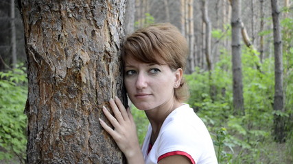 Sad young woman in autumn forest hugging the pine