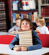 Schoolboy Resting Chin On Stack Of Books At Table In Library