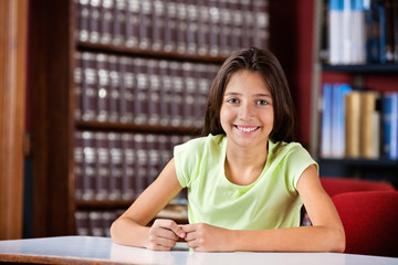 Happy Schoolgirl Sitting In Library