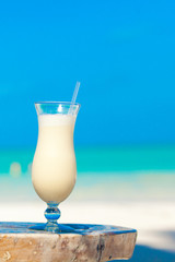 White pina colada on the table on the beach
