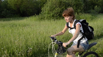 Young woman on a bicycle ride to the meeting to the sun