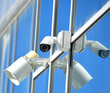 CCTV camera and loudspeaker on a glass facade outdoors