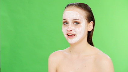 Beautiful woman with clay facial mask over green screen