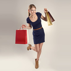 Attractive slim girl showing shopping bags happily.