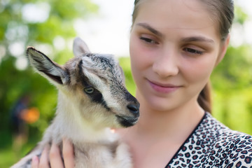 woman holding a little young goat