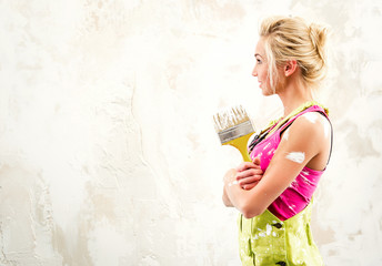 Female in coverall holding paint brush over obsolete background