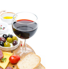 glass of red wine and appetizers - cheese, bread, salami, olives