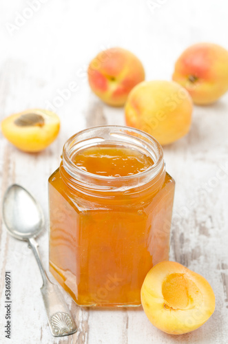 apricot marmalade in a glass jar and fresh apricots