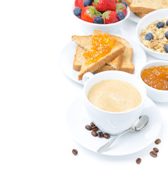cup of cappuccino, toast with orange jam, berries and muesli