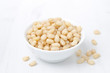 pine nuts in a bowl on a white background
