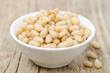 pine nuts in a bowl on wooden background close-up