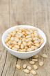 pine nuts in a bowl on wooden background