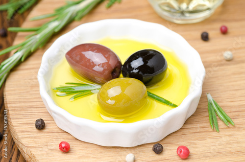 three kinds of olives and fresh rosemary in bowl with olive oil