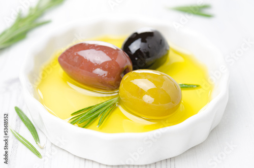 three kinds of olives and rosemary in bowl