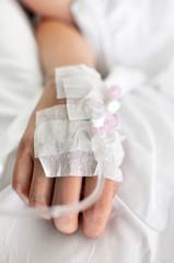 Mano di giovane donna con la flebo nel letto di ospedale