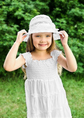 Portrait of adorable smiling little girl in white dress and hat
