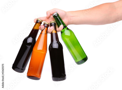 four beer bottles in different colours and hand
