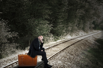 Businessman sitting on his case and waiting for the train