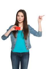 Young teen female holding blank credit card and pointing to side